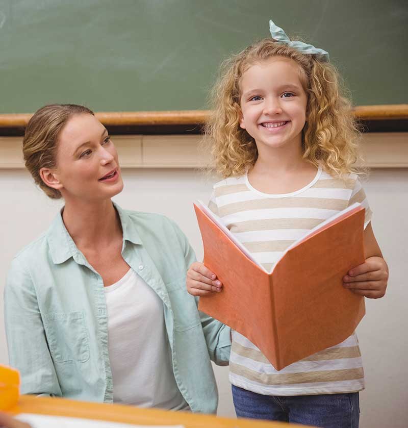 Girl reading with teacher